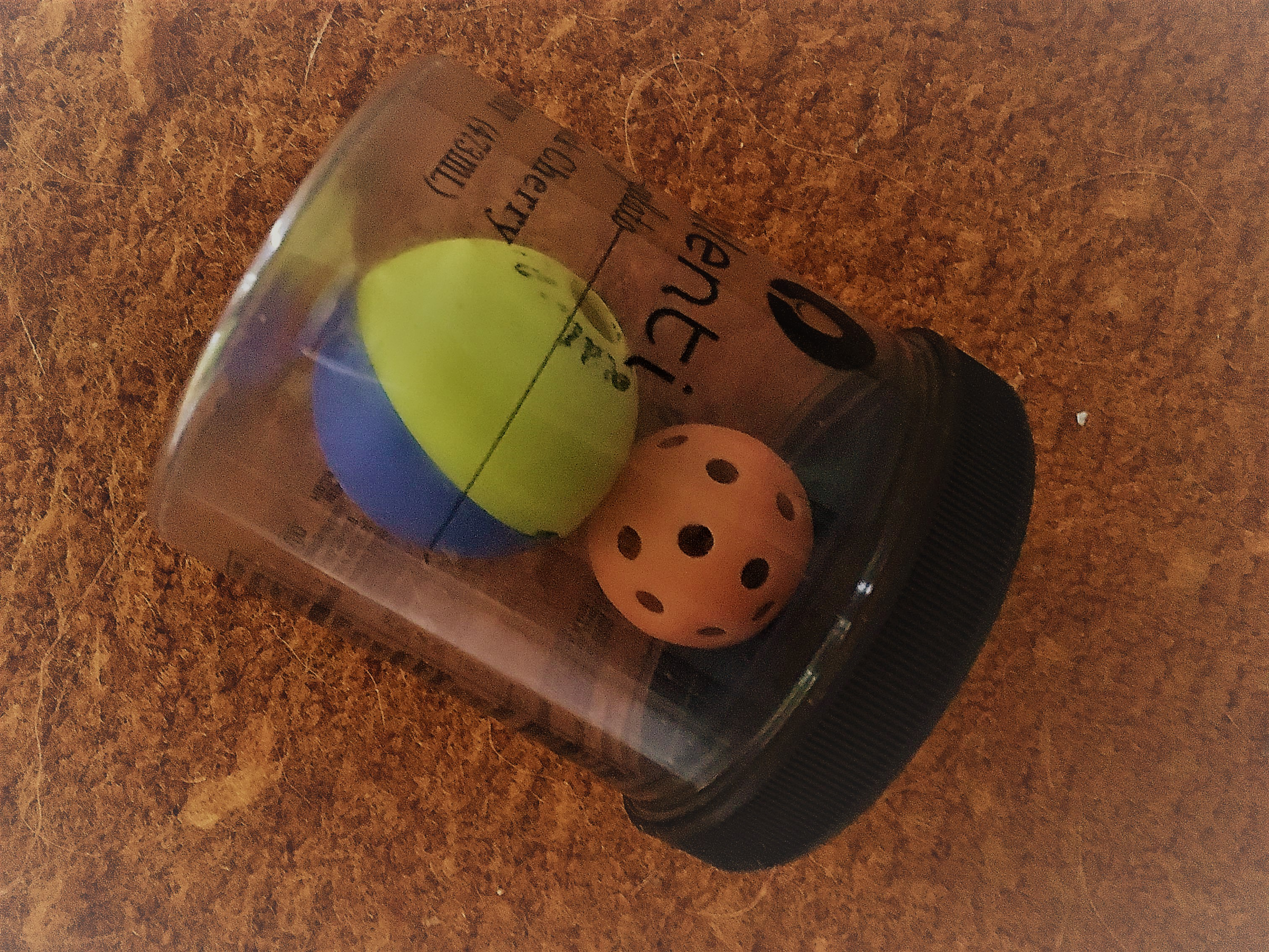 An Our Pets ball and a foraging ping-pong, stuffed and placed inside larger object.